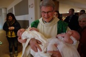 Father Tom carries around the new baby Christians and presents them to the Church, the family!